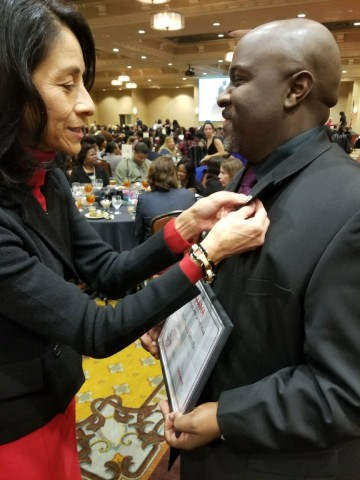 Dr. Lupita Hinojosa, Spring ISD chief school leadership and support services officer, from left, pins a Spring ISD pin on Richard Smith's lapel after he was recognized as a Houston Area Alliance of Black School Educators Campus Teacher of the Year.