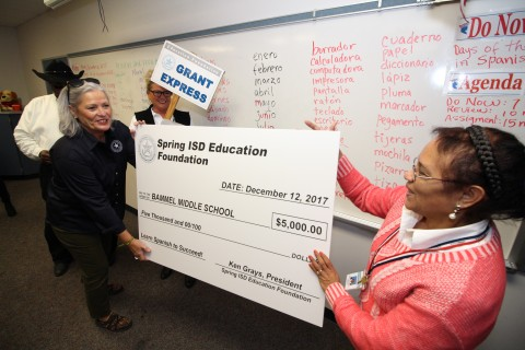 Jill Wright, from left, delivers a grant check to Bammel Middle School teacher Itzelda Lascano from the Spring ISD Education Foundation.